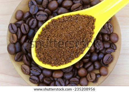 A spoon of freshly ground coffee on coffee beans - stock photo
