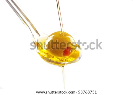 A spoon with an olive under a fall of oil