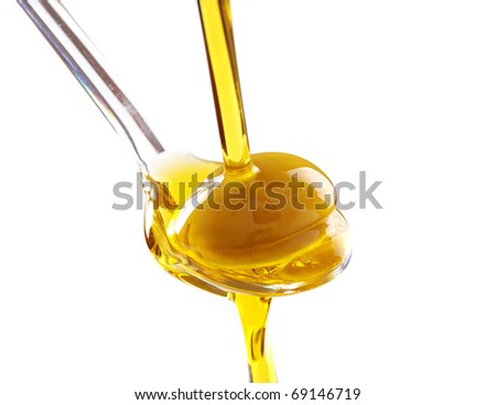 A spoon with an olive under a fall of oil - stock photo