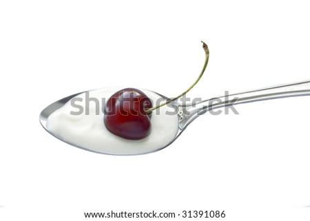 A spoon with yogurt and  a cherry on top isolated