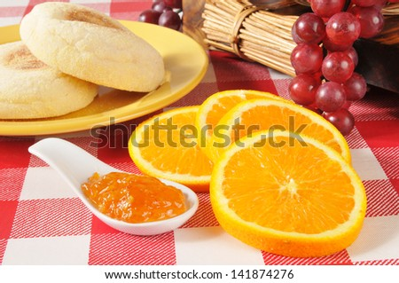 A spoonful of orange marmalade and English muffins - stock photo