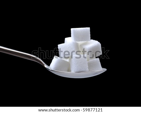 a spoonful of sugar cubes on black - stock photo