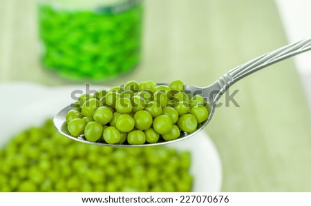 A spoonful of tinned canned green peas - stock photo