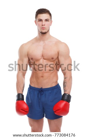 A sportsman in shorts and boxing gloves stands and looks with a serious . Isolation.