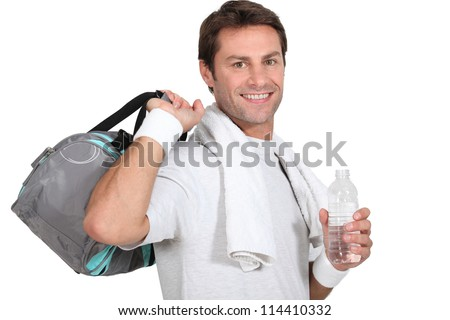 A sportsman smiling at us and holding a bag and a bottle of water. - stock photo