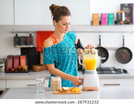 A sporty woman is standing in her kitchen, making a smoothie with fresh, seasonal fruits, nuts, and oats, to complete her healthy start to the morning. - stock photo