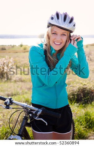 A sporty woman riding a bicycle outdoor - stock photo