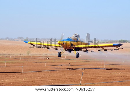 A spray plane or crop duster applies chemicals to a field of crops. - stock photo