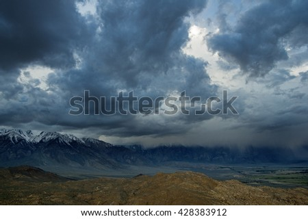 a spring storm comes in over the Eastern Sierra over the Owens Valley - stock photo