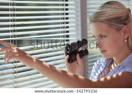 A spy peering through some blinds - stock photo