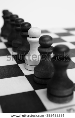 A squad of black pawns on chessboard. One white pawn. At home Among Strangers. Spy. Figures stand in a row. Selective focus, close up view. Vintage toning. Black and white.