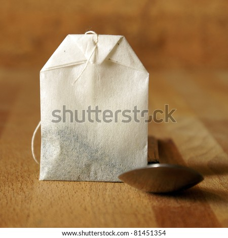 A square format shot of a tea bag and spoon for preparing the beverage. - stock photo