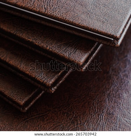a stack of books in a brown leather hardcover, closeup - stock photo