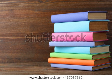 a stack of books in beautiful covers on wooden background