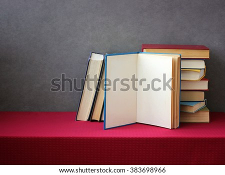 A stack of books in the colored covers on the table with a red tablecloth. Still life with books. - stock photo