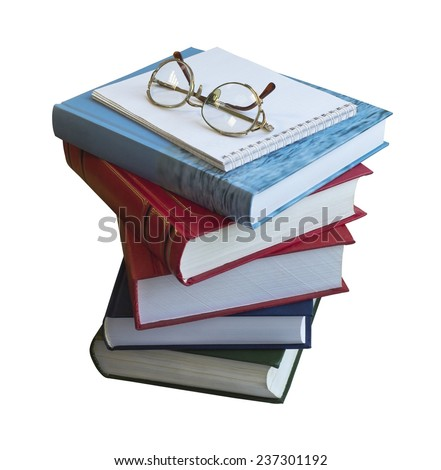 A stack of books, notebook and glasses on isolated background