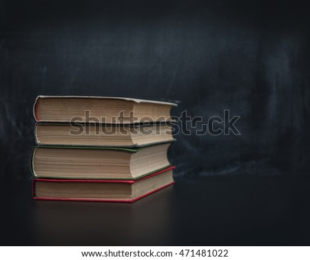 A stack of books on black background blackboard