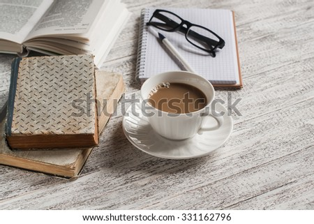 A stack of books, open  clean notepad, glasses and a cup of cocoa on a white wooden table. The concept of education and training - stock photo