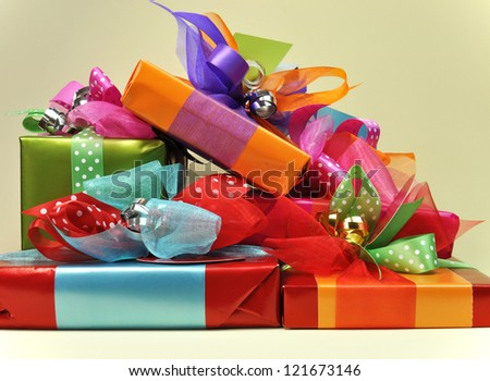 A stack of bright color presents in red, blue, orange, pink and green, with ties, tags and ribbons. - stock photo