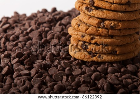 A stack of chocolate chip cookies sits on a pile of chocolate chips.
