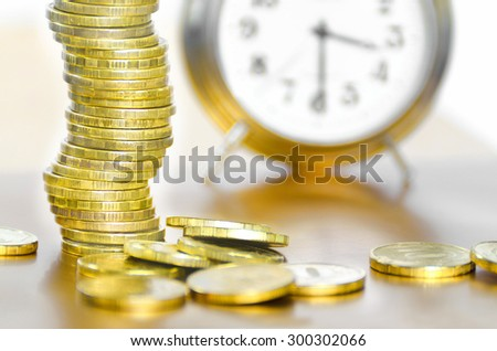 A stack of coins and alarm clock - stock photo