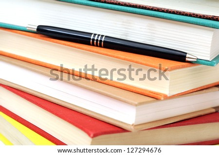a stack of colorful books and pen for background uses - stock photo