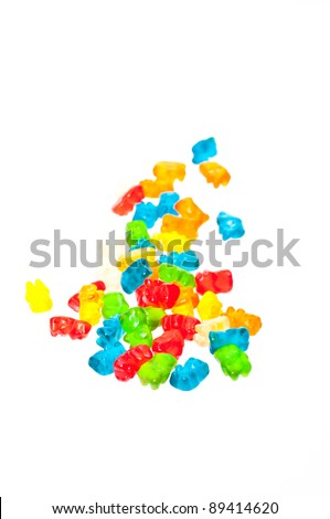 A stack of colorful gummy bears and six colorful gummy bears line up
