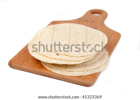 A stack of corn tortillas on a wooden cutting board. - stock photo
