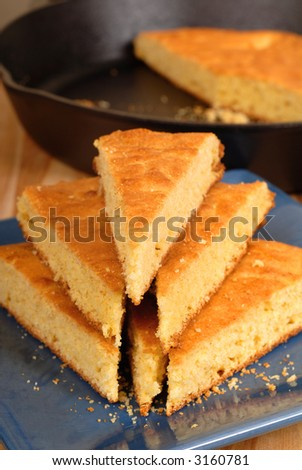A stack of cornbread on blue plate with black skillet in background - stock photo