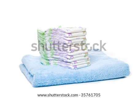 A stack of diapers on a blue towel with white background