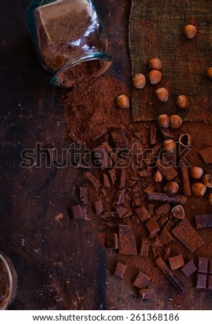 A stack of different chocolates, lots of grated chocolate, slices of dark and milk chocolate, cacao powder and hazelnut kernels, taken on dark vintage table. Rustic style. Top view.  - stock photo