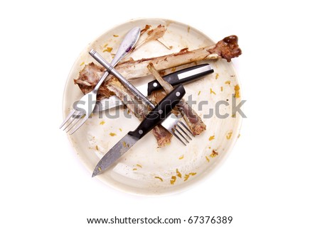 A stack of dirty plates with bones. - stock photo