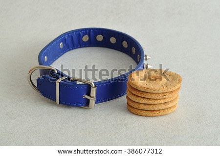 A stack of dog biscuits and a blue spike dog collar displayed on a white background - stock photo