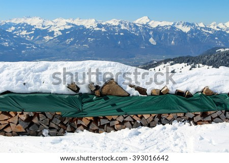 A stack of firewood in a snowy mountainous setting. - stock photo