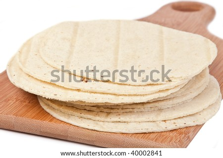 A stack of freshly made corn tortillas on a wood cutting board.