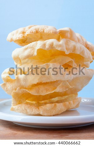 A stack of freshly made poppadoms against a light blue background - stock photo
