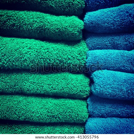 A stack of green and blue terry towels. - stock photo