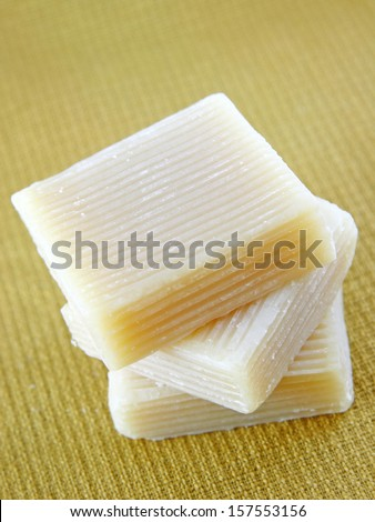 A Stack of Home made soap with natural goat milk as main ingredient on a yellow fabric background.  - stock photo