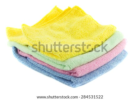 A stack of multi-colored towels stacked in the shape of a square on a white background - stock photo