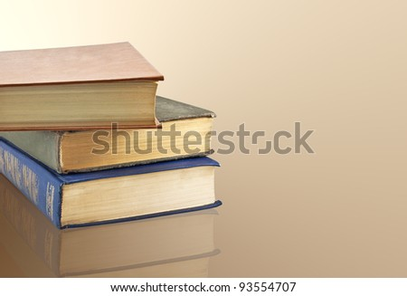 A stack of old books on the reflective surface - stock photo