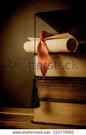 A stack of old books, topped with a mortarboard and  diploma scroll, tied with red ribbon.  Aged and vignetted for vintage effect.  Blackboard in background provides copy space to left. - stock photo