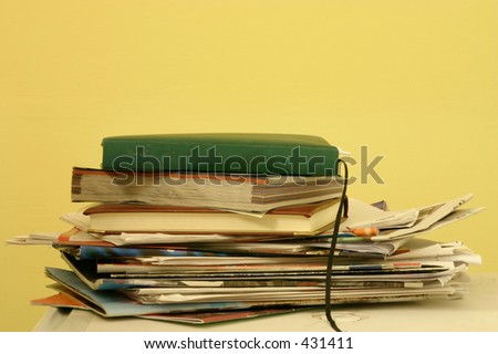 A stack of old magazines and diaries on a white table with a yellow background, with space for designers to add things