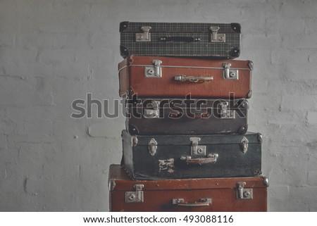 A stack of old suitcases on a background of a brick wall
