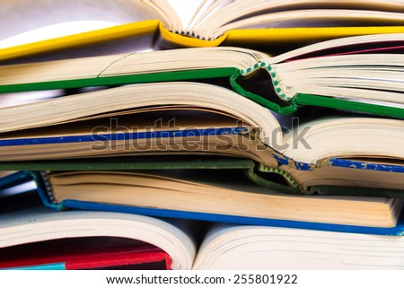 A stack of open, colorful book with a white background - stock photo