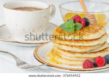 A stack of pancakes drizzled with honey and decorated with ripe raspberries and blueberries and a cup of tea