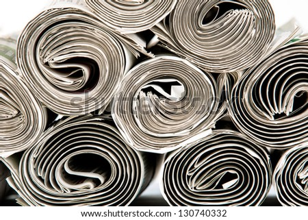 A stack of rolled up newspapers - stock photo