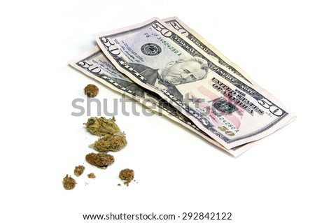 A stack of three 50 dollar US bills is shown behind a cluster of marijuana pot buds, over white. - stock photo
