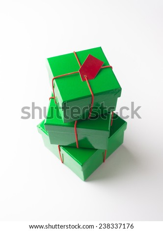 A stack of  three green color festive gift boxes on white background. - stock photo