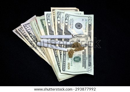 A stack of  US dollar bills is shown fanned out under a cluster of marijuana pot buds and three joints, over black. - stock photo