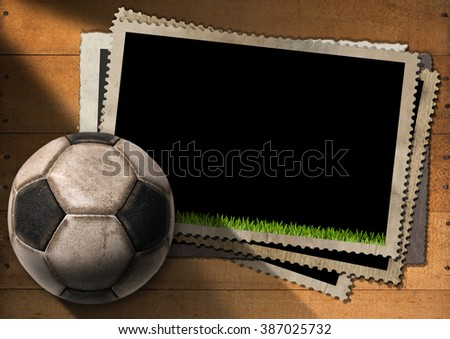 A stack of vintage and blank photo frames with an old soccer ball (football). On a wooden background - stock photo